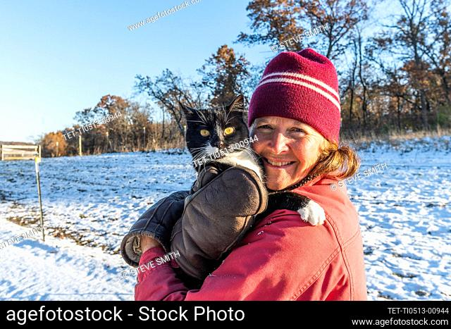 Woman holding cat in snow