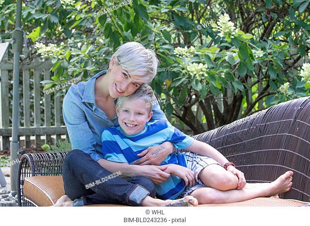 Caucasian woman hugging son on sofa outdoors