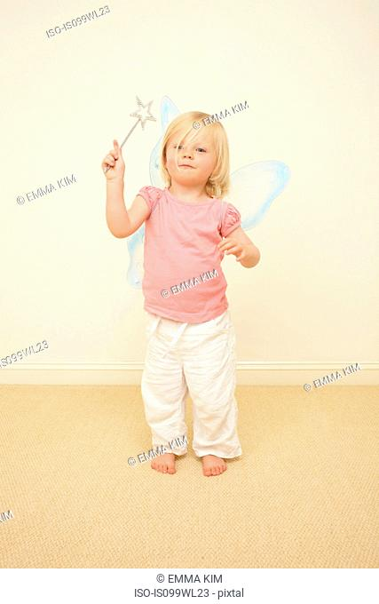 Toddler wearing wings, holding wand