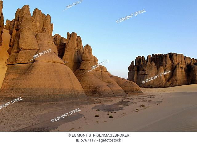 Eroded rock formations rising out of desert sand in Tin Akachaker, Tassili du Hoggar, Wilaya Tamanrasset, Algeria, Sahara, North Africa