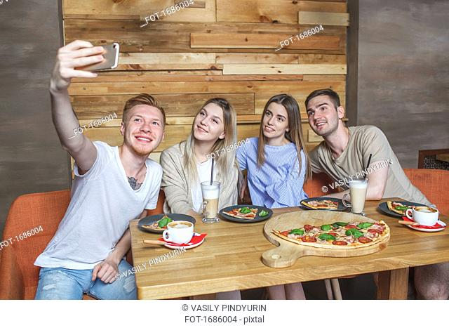 Young friends taking selfie while sitting at restaurant
