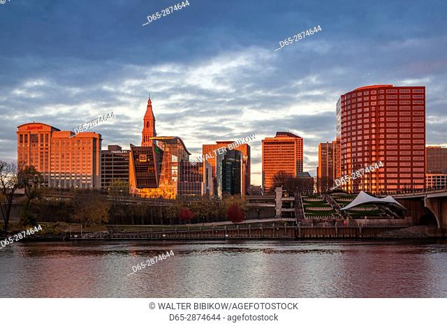 USA, Connecticut, Hartford, city skyline with Connecticut Science Center and Travelers Building, from the Connecticut River, dawn, autumn