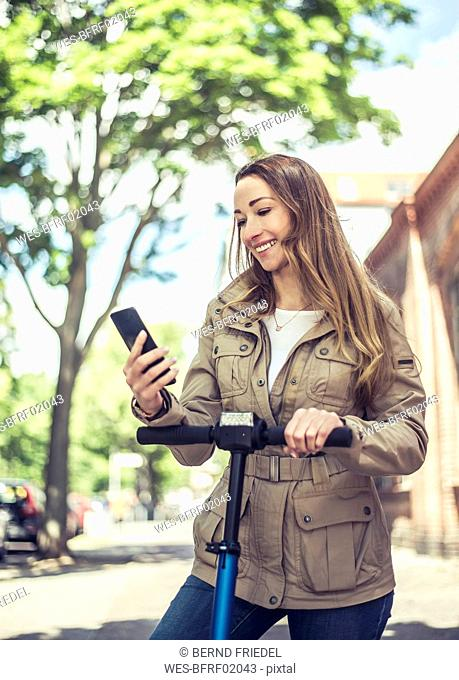Portrait of smiling woman with E-Scooter looking at smartphone