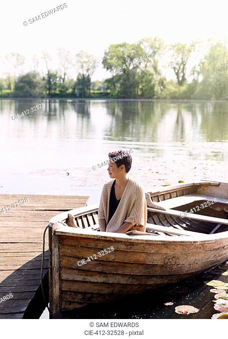Serene woman sitting in canoe at sunny lakeside dock