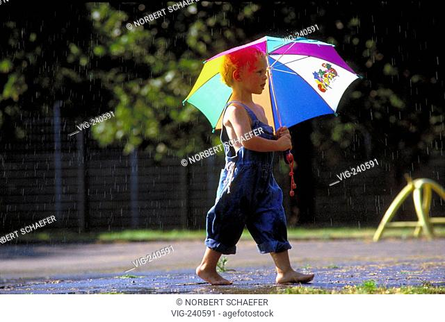 portrait, blond boy, 4 years, is walking barefoot with umbrella by rain and sunshine  - 0, GERMANY, 26/07/2002