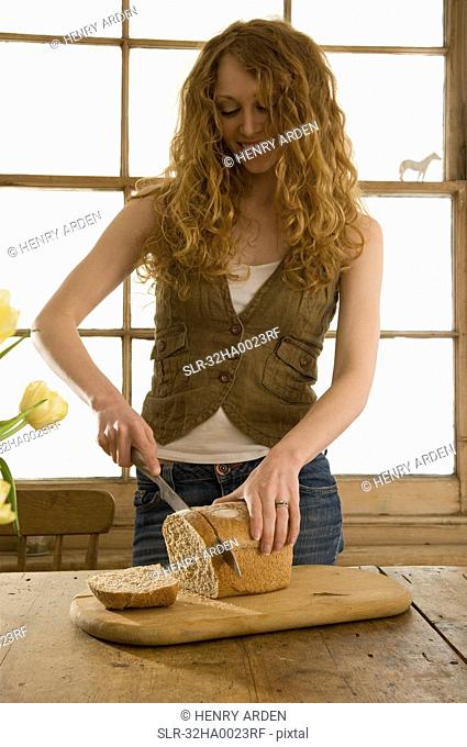 Woman slicing bread in kitchen