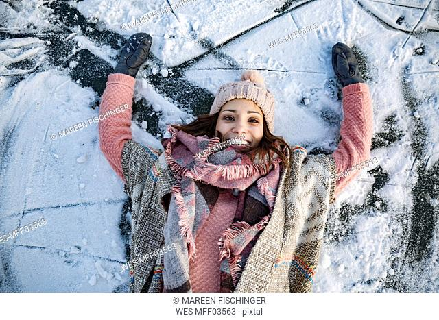 Portrait of happy woman lying down on frozen lake surface