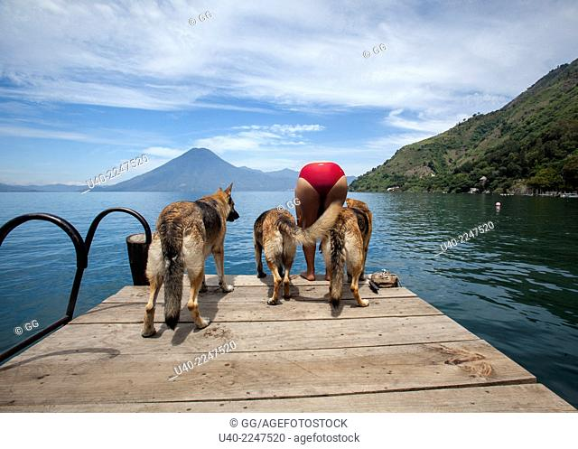 Guatemala, Lake Atitlan, Jaibalito, German shepherds with owner on dock