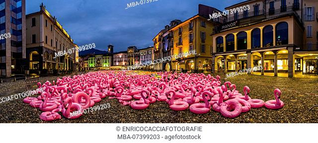 Panorama of the Piazza Grande in Locarno in the evening with art installation made of pink plastic flamingos