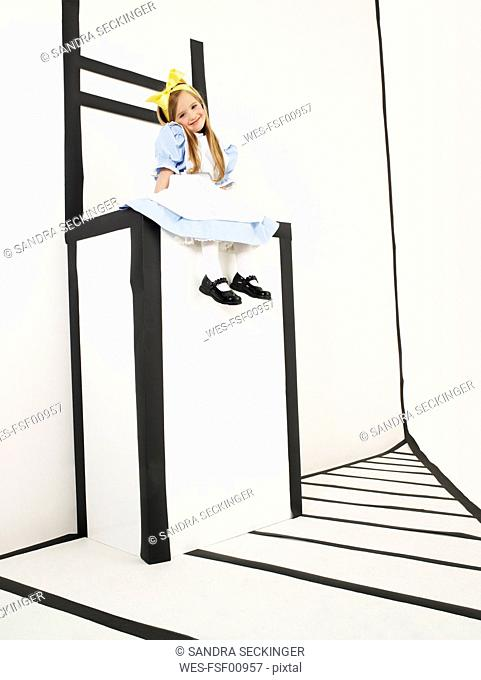 Smiling little girl dressed up as Alice in Wonderland sitting on oversized chair