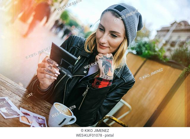 Young tattooed woman sitting in a pavement cafe looking at photos