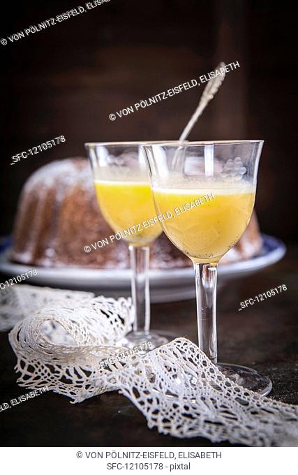 Two glasses of eggnog in front of an eggnog cake