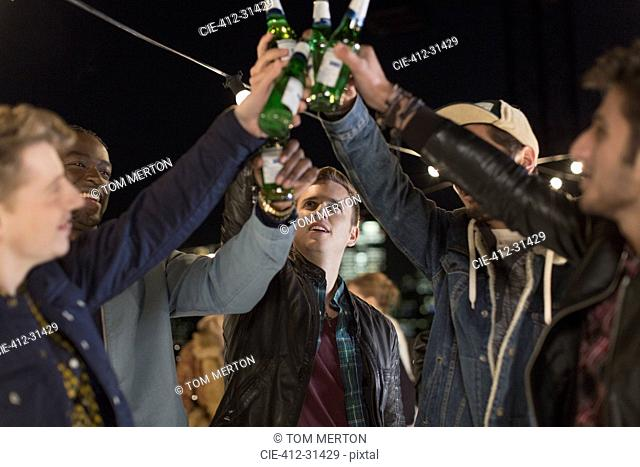 Young men toasting beer bottles at party