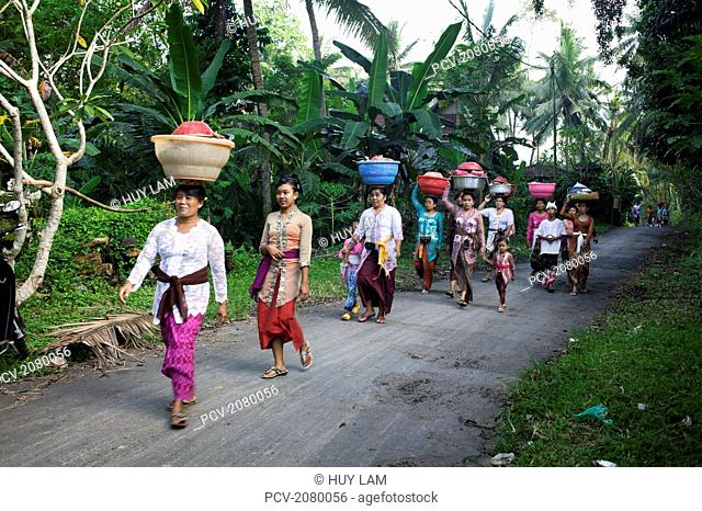 Women walking down a road with baskets on their heads during Kuningan Festival; Bali, Indonesia