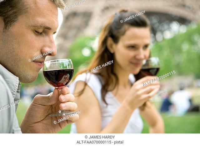 Man enjoying bouquet of red wine outdoors