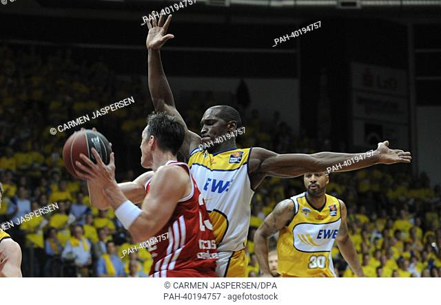 Oldenburg's Rickey Paulding (C) tries to stop Bamberg's Casey Jacobsen (front) during the final match of the Bundesliga Basketball Playoffs (Best of 5) between...
