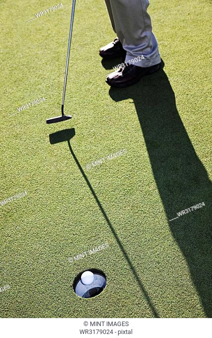 Closeup of golfer hitting a put and a golf ball going into the cup