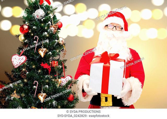 santa claus with gift box at christmas tree
