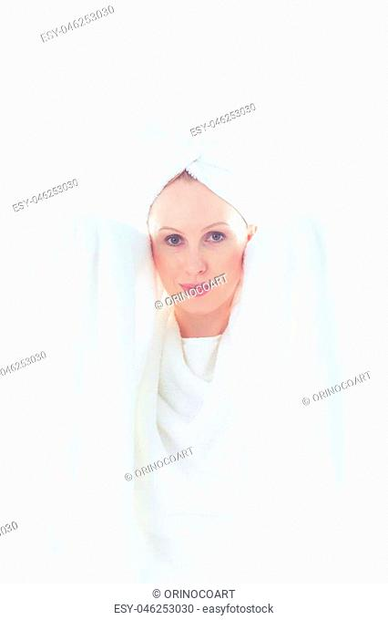 Beautiful young woman covers her nude body with white towels while looking into the camera and wearing another towel on her head, isolated on white background