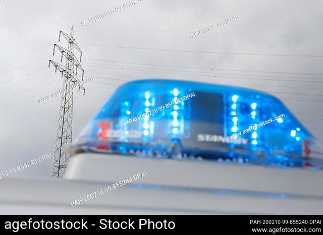 10 February 2020, Nrw, Duisburg: A police car with a blue light is standing in front of a power pole, where there is a problem with the high-voltage line...