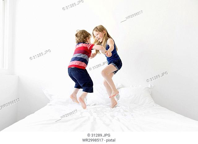 A six year old girl and four year old boy, brother and sister jumping up and down on a double bed