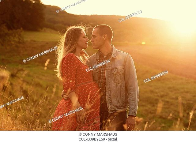 Romantic mid adult pregnant couple face to face on hillside at sunset