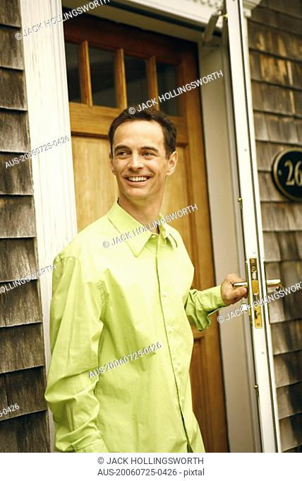 Close-up of a mature man holding a door handle and smiling