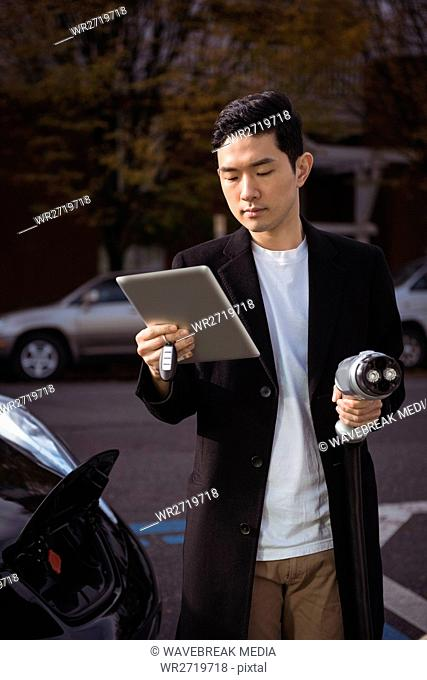 Man using digital tablet while holding car charger