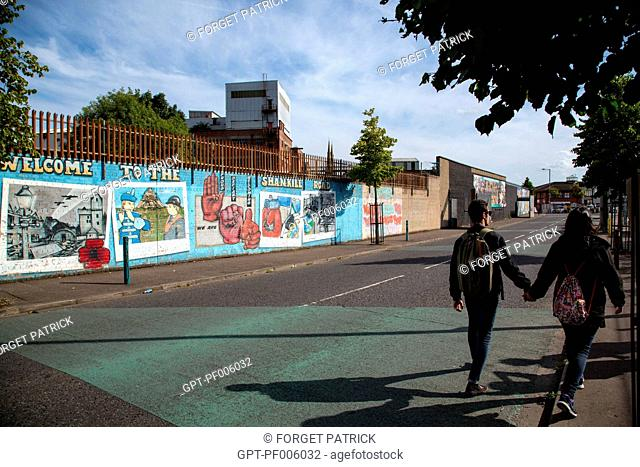 COUPLE STROLLING PAST THE WALL OF PEACE ON SHANKILL ROAD, REMEMBRANCE OF THE NORTHERN IRELAND RIOTS, NORTHUMBERLAND STREET, BELFAST, ULSTER, NORTHERN IRELAND
