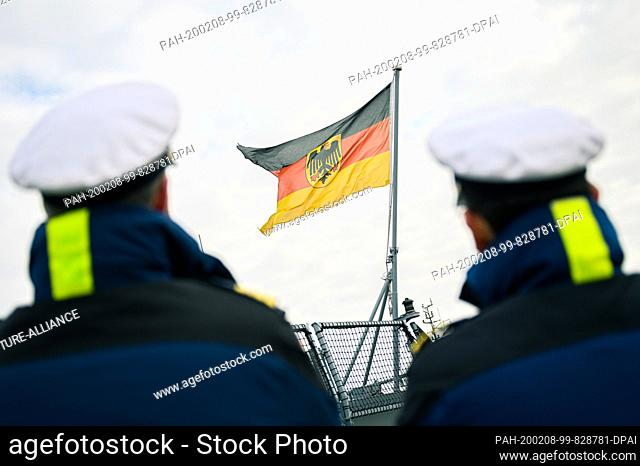 """08 February 2020, Lower Saxony, Wilhelmshaven: Two marines stand at the harbour of the naval base Wilhelmshaven and watch the return of the frigate """"""""Hamburg"""""""""""