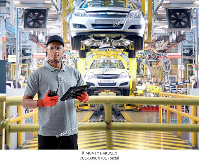 Composite image of car worker using digital tablet on production line in car factory