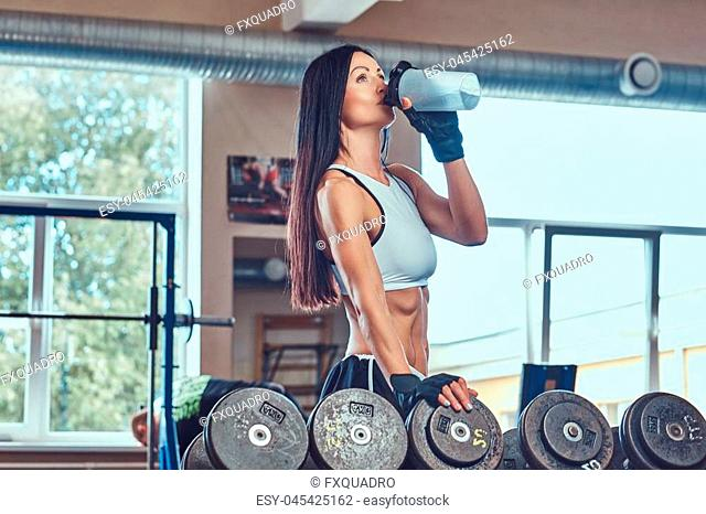 A beautiful sexy athletic brunette female in a sportswear, drink water near a counter with dumbbells
