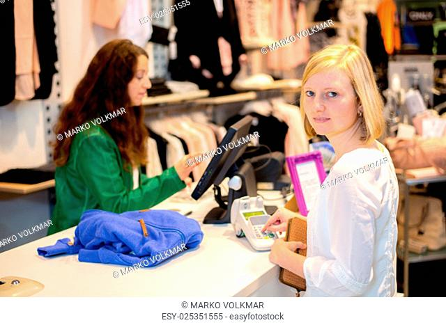 young woman in the clothes shop over the counter