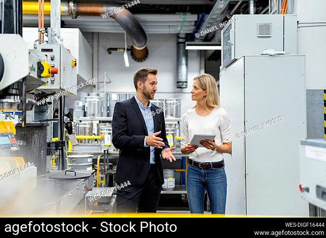 Businesswoman with digital tablet listening to manager while standing in factory