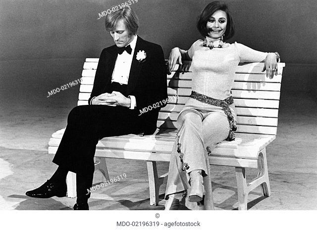 Dancer and presenter Raffaella Carrà sitting on a bench with Italo-French Nino Ferrer during the TV programme Io, Agata e tu. Rome, March 1970
