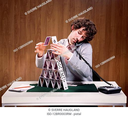 Businessman stacking cards on desk