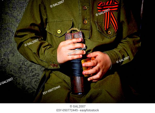 Hands of a little boy on the background of a military uniform with St. George's ribbon
