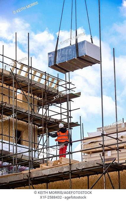 UK house construction: a worker working on a site erecting timber-framed buildings