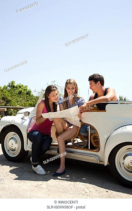 Young friends with convertible car looking at map