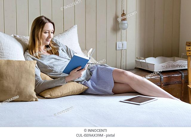 Woman sitting on bed reading book