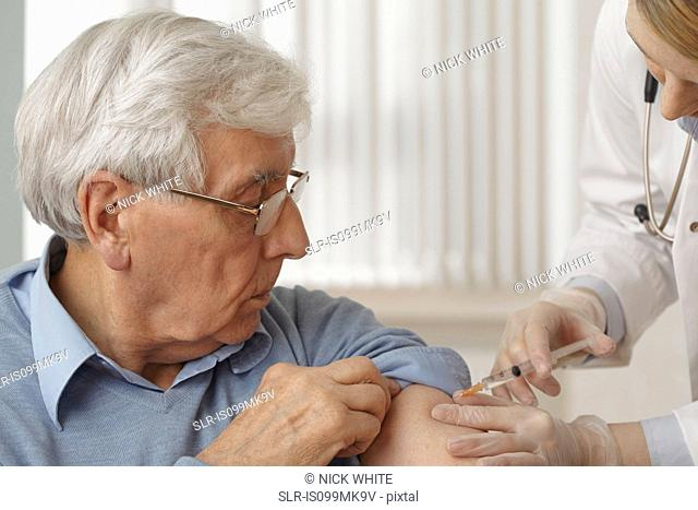 Doctor giving senior man injection