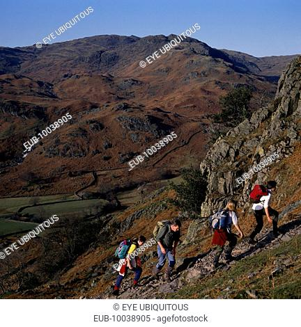Walkers on footpath to Helm Crag above Grasmere with view west to Sour Milk Gill