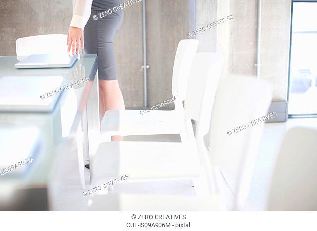 Young woman preparing boardroom table