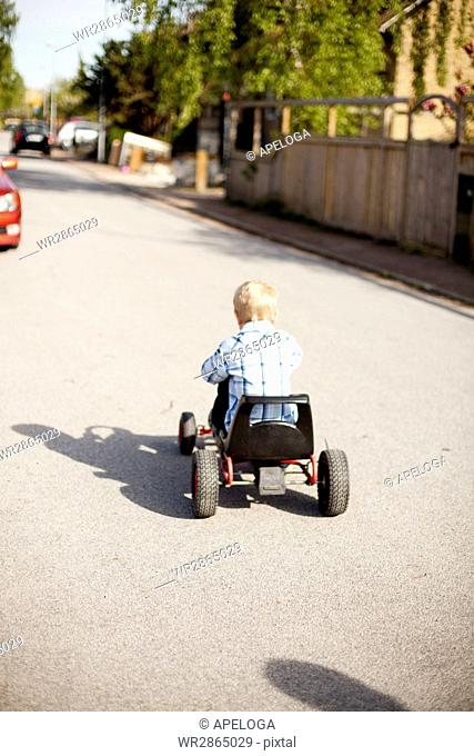 Rear view of boy riding quadricycle on street