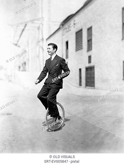 Profile of a young man riding a unicycle All persons depicted are not longer living and no estate exists Supplier warranties that there will be no model release...