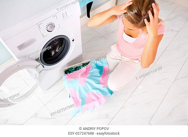 Young Shocked Angry Woman Looking At Stained Bleached Clothes Near Washing Machine At Utility Room
