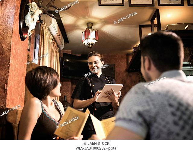 Couple in restaurant with waitress taking the order