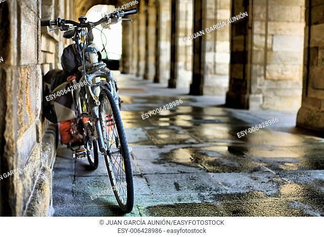 A bicycle rests under the arcades of the City of Santiago de Compostela