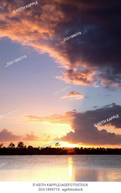 Sunset and sunbeams through a thunderstorm over swamp lake scene at the Everglades National Park, Florida, USA
