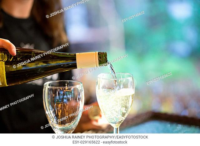 Bartender pouring white wine into a glass at a wedding reception